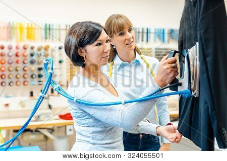 Two women in a dry-cleaning company ironing clothes on a hanger