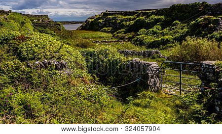 View Of The Irish Countryside Between Stone Fences With A Metal Gate On The Island Inis Oirr With Th