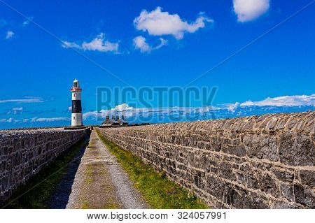 Straight Rural Road Between Limestone Fences In The Direction Of The Lighthouse In Inis Oirr Island,