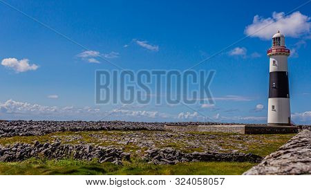 Beautiful View Of The Lighthouse On The Rocky Limestone Coast Of The Island Inis Oirr, Wonderful Sun