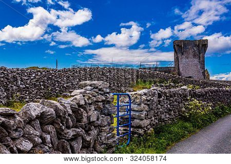 Limestone Fences With A Blue Metal Gate Beside A Rural Road On Inis Oirr Island With The Ruined 19th