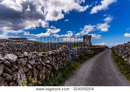 Rural Road Between Limestone Fences On The Inis Oirr Island With The Ruined 19th Century Tower (a Tú
