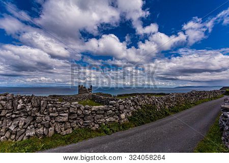 Rural Road Between Limestone Fences On Inis Oirr Island With The Ruined Castle Tower (caisleán Ui Bh