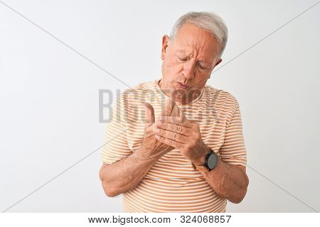 Senior grey-haired man wearing striped t-shirt standing over isolated white background Suffering pain on hands and fingers, arthritis inflammation