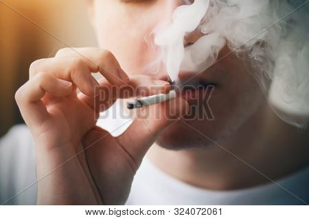A Young Guy With Bristle On His Face Exhales Thick Smoke From A Cigarette He Smokes And Enjoys The M