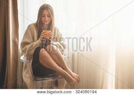 Woman With Cup Of Hot Drink By The Window. Looking At Window And Drink Tea. Good Morning With Tea. A