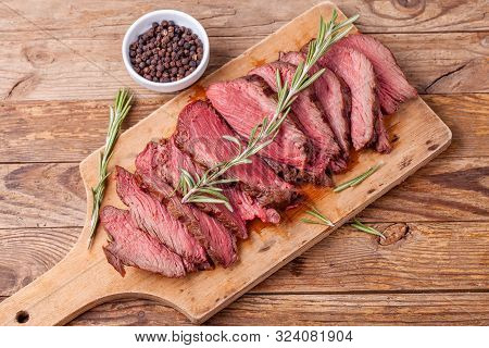 Slices Of Medium Rare Roast Beef Meat On Wooden Cutting Board, Pepper And Rosemary Branches On Woode