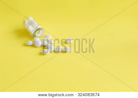 White Medical Pills From Glass Bottle On Light Yellow Background  With Copy Space. Pharmacy Theme, C