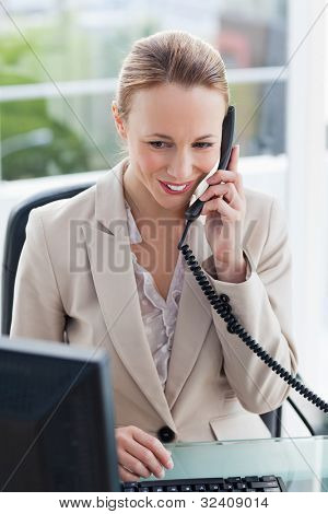 Woman in a suit on the phone in her office with city view in background