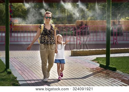 Young Mother With Her Daughter In Hot Weather, Cool Off At The Gates Of Climate Control In The Water