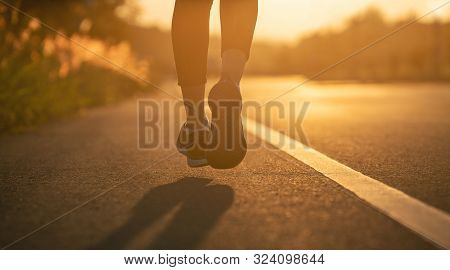 Runner Feet Running On Road Closeup On Shoe. Woman Fitness Sunrise Jog Workout Wellness Concept. You