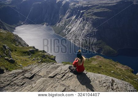 Girl Dressed In Red Shirt Contemplates The Fjord. The Weather Is Good, So Water Is Blue, Rocks Are S