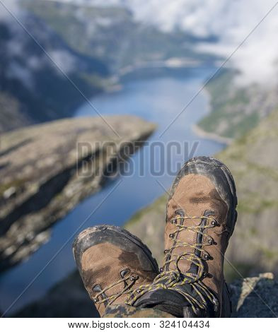 Hiking Boots In Foreground. Troll Tongue (trolltunga) And Norway Fjord In The Background.