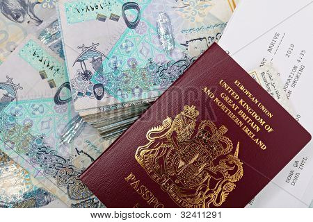 A new British passport with a booking form for a flight to Doha, Qatar, and a boarding pass on top of tens of thousands of Qatari riyals. A business opportunity or expat contract perhaps