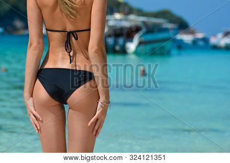 Sexy Woman Buttocks On Tropical Beach Background Near Ocean. Young Woman In Black Bikini, Sunbathing
