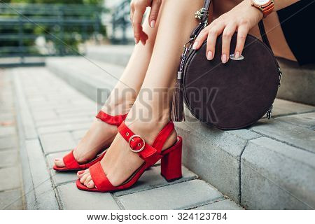 Stylish Shoes And Accessories. Young Woman Wearing Fashionable Red High-heeled Sandals And Holding H