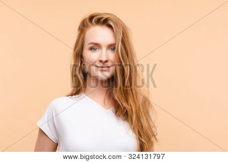 Pretty Jovial Smiling Girl With Redhair.isolate On Pale Yellow Background.