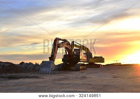 Heavy Tracked Excavators At A Construction Site On A Background  Sunset. Special Heavy Construction