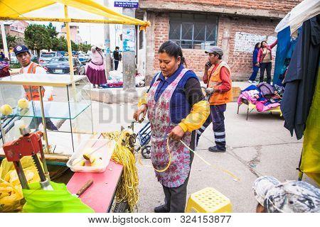Puno, Peru - Jan 5, 2019: Local woman sells peeled orange juice on street of Puno, Peru . South America.