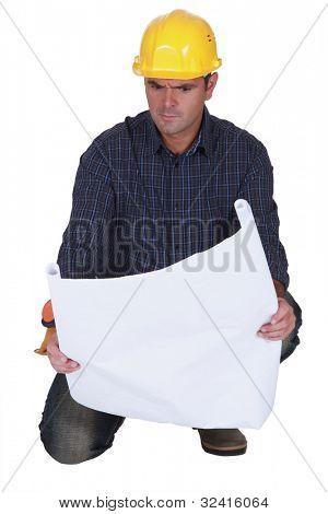 Angry tradesman looking at a technical drawing