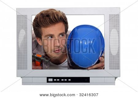 Young man and his hard hat stuck in a television screen