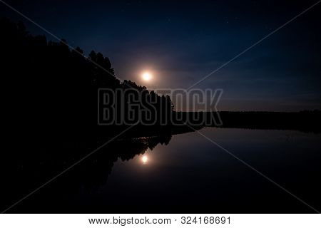 Moon Rise Over A Mountain Lake With Reflection