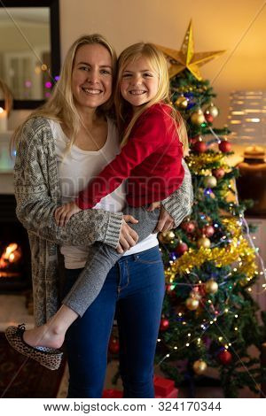 Front view of a young Caucasian woman holding her young daughter in their sitting room at Christmas time beside a decorated Christmas tree smiling to camera