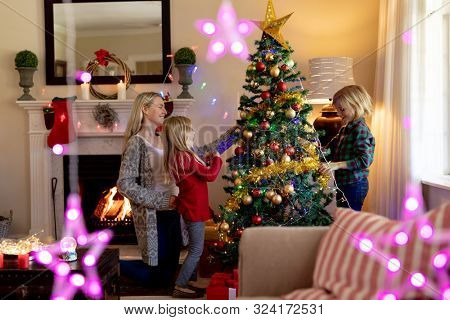 Side view of a young Caucasian woman and her young son and daughter decorating the Christmas tree in their sitting room at Christmas time, with Christmas star decorations hanging in the foreground