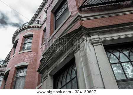 Red Brick, Gray Stone, And Wrought Iron Details On The Exterior Of An Old Brownstone Apartment Build