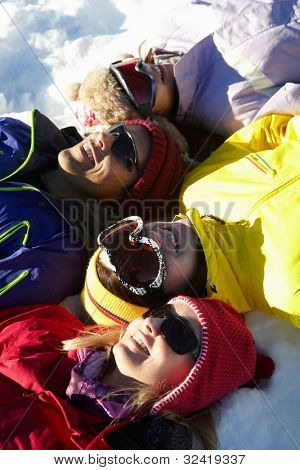 Overhead View Of Teenage Family Lying In Snow On Ski Holiday In Mountains