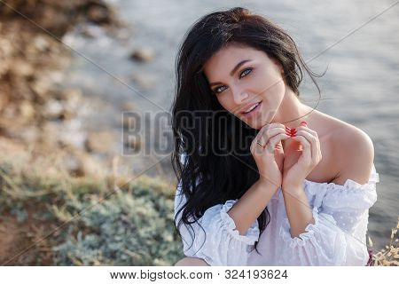 Happy Woman On The Beach. Portrait Of A Beautiful Girl Close-up On Sea Background. Spring Portrait O