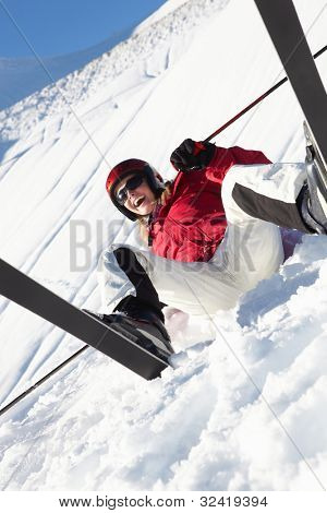 Female Skier Sitting In Snow With After Fall