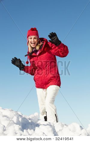 Woman Standing In Snow Wearing Warm Clothes On Ski Holiday In Mountains
