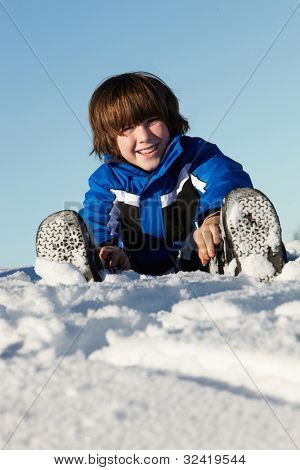 Young Boy Playing In Snow On Holiday In Mountains