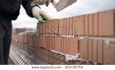 Worker In Close Up Of Industrial Bricklayer Installing Bricks And Mortar Cement Brick On Constructio