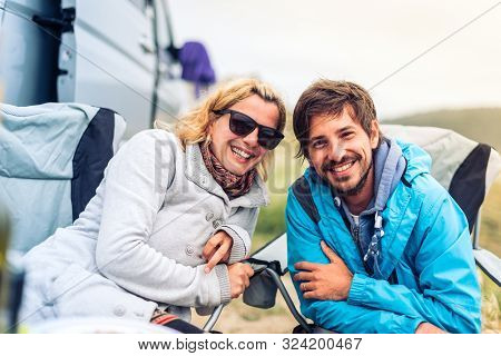 Young Couple Smiling With Motorhome, Rv Or Campervan On Beach.