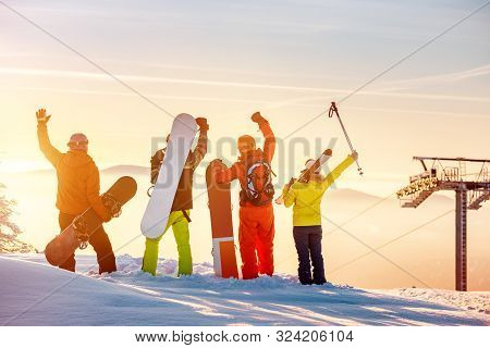 Group Of Happy Friends Skiers And Snowboarders Stands At Sunset Mountain Top And Having Fun
