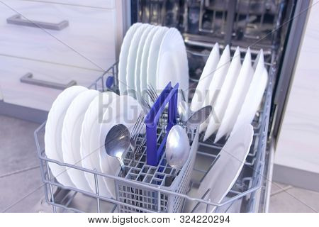 Clean White Dishes And Cutlery In Basket Of Built-in Dishwasher In Kitchen. Open Dishwasher Mashine