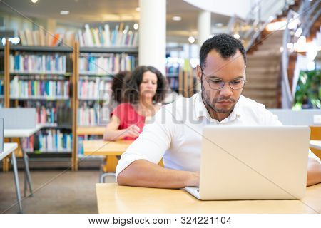 Focused Male Adult Student Working On Computer In Classroom. Serious Latin Man Sitting At Desk And U