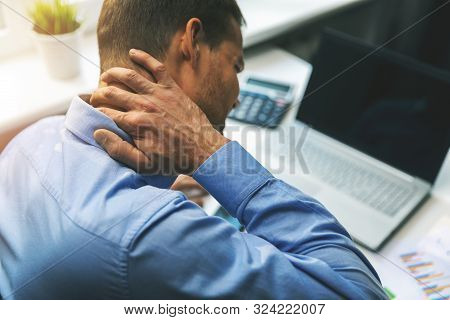 Office Syndrome - Man Suffering From Neck And Back Pain While Working With Computer
