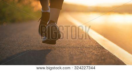 Runner Feet Running On Road Closeup On Shoe. Woman Fitness Sunrise Jog Workout Wellness Concept. You