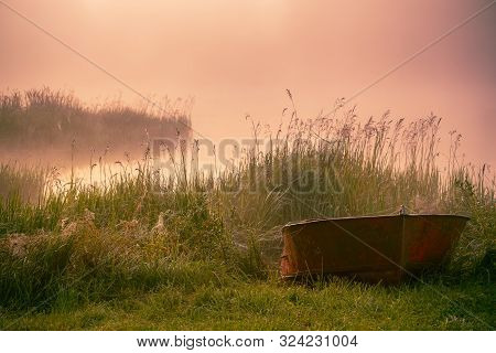 The Boat Lies In The Green Grass In Fog And Sunlight.