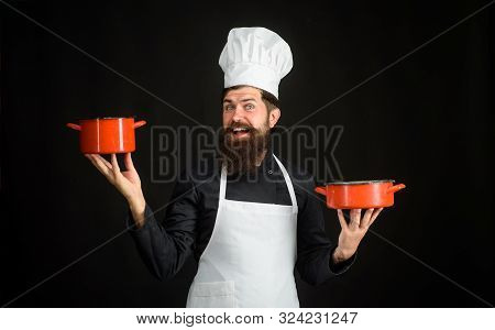 Male Chef, Cook, Baker In Uniform Holds Saucepan In Hands. Chief Man In White Apron With Pots. Beard