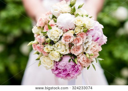Bridal Bouquet. Wedding Bouquet In The Hands Of The Bride. Outdoor Shot In A Sunny Day With Green On