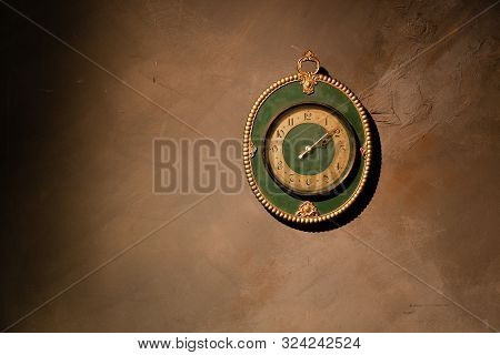 Gold Vintage Clock With Arabic Numbers. Beautiful Green Frame Clock Hanging On The Brown Wall. Antiq