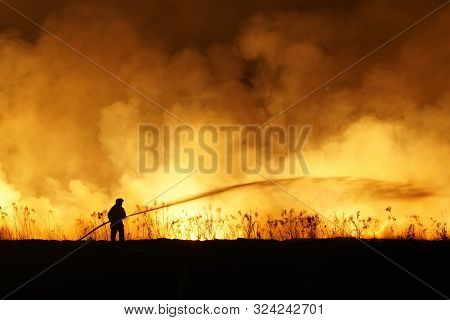 Silhouette Of Fireman Fighting Bushfire At Night, Man Against The Fire.