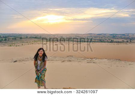 Single Asian Girl Smiling To Camera On Red Sand Dune When Daybreak At Muine, Vietnam