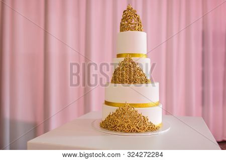 Wedding Cake, On White Table. 3-tiers Covered In Ivory Fondant Sprayed With Pearl Spray And Gold Ros