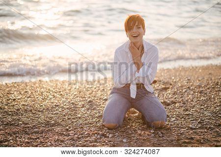 Beautiful Sensual Woman With Short Haircut Posing On The Beach At Sunset.