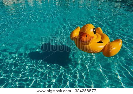 Bright Yellow Inflatable Swimming Duck In Ripple Blue Water In Swimming Pool Of Resort Hotel With Su